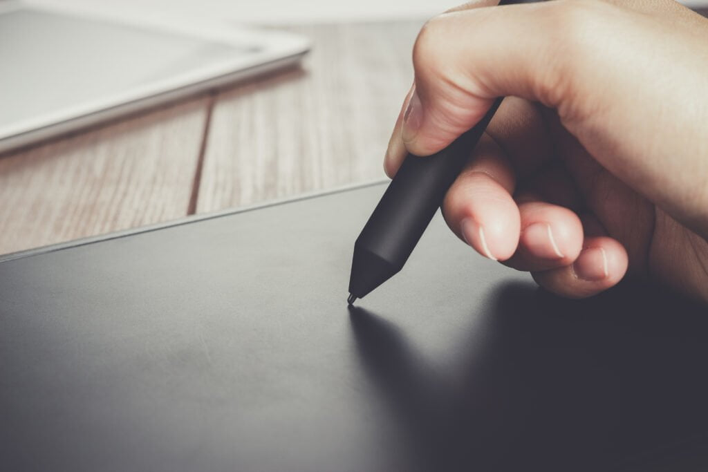 hand of the designer with a pen on tablet