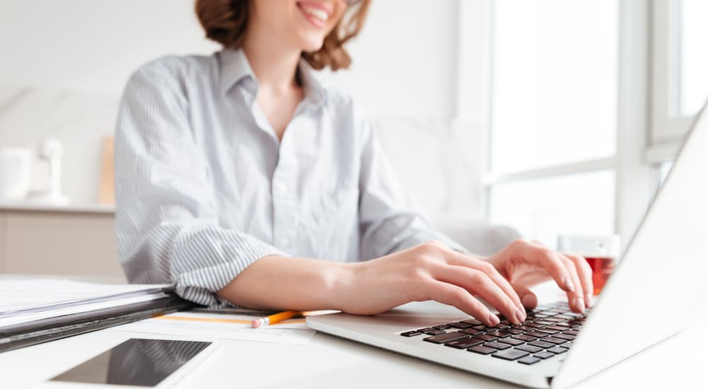 A smiling woman is researching web hosting on her laptop.