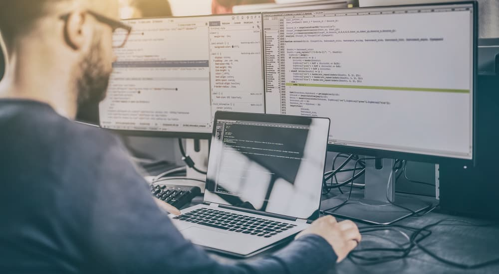 A man with two monitors and a laptop is coding a website.