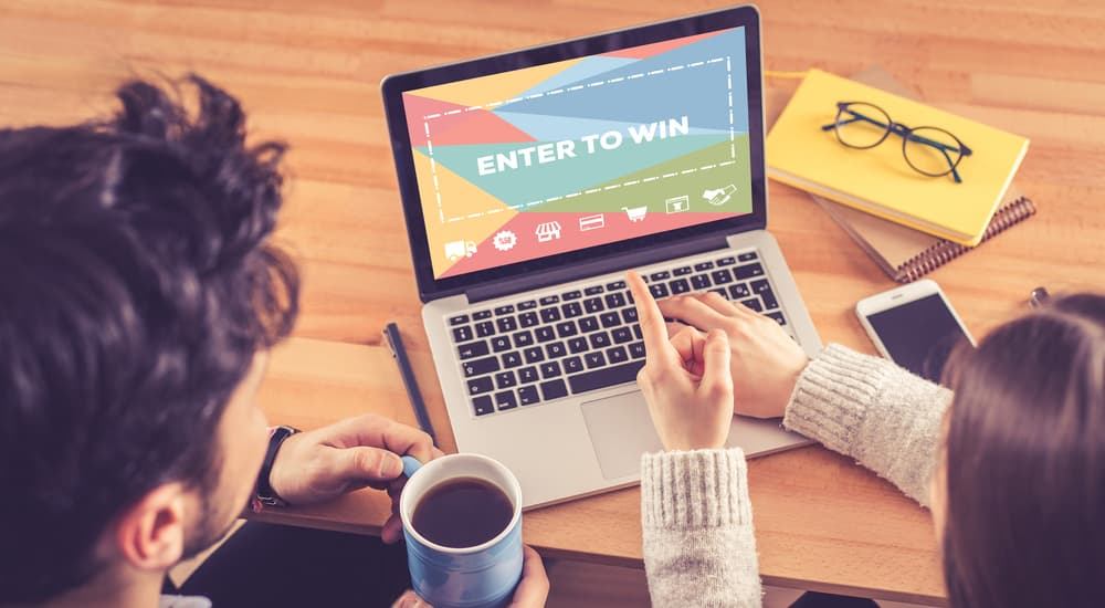 Two people are looking at a laptop that says 'enter to win'.